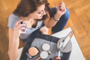 woman applies fragrance