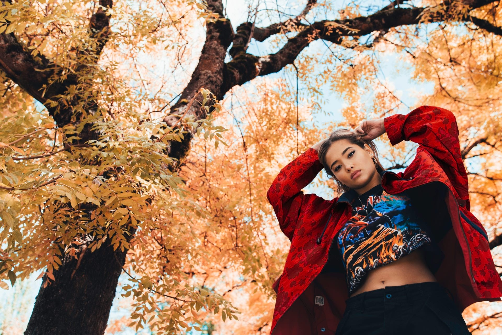 fashionable woman standing near fall tree