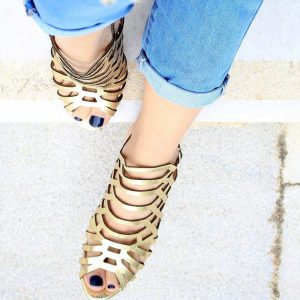 woman wearing gold gladiator sandals